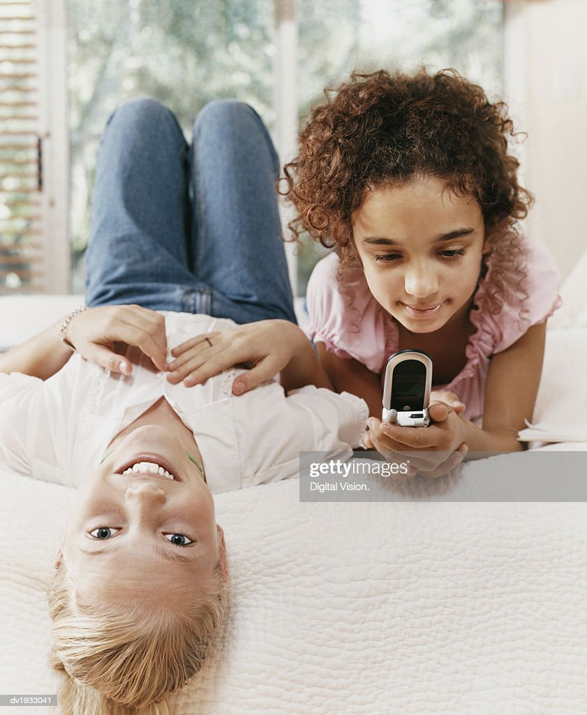 Two Young Girls Lie Side by Side on a Bed, One Texting on Her Mobile Phone : Stock Photo