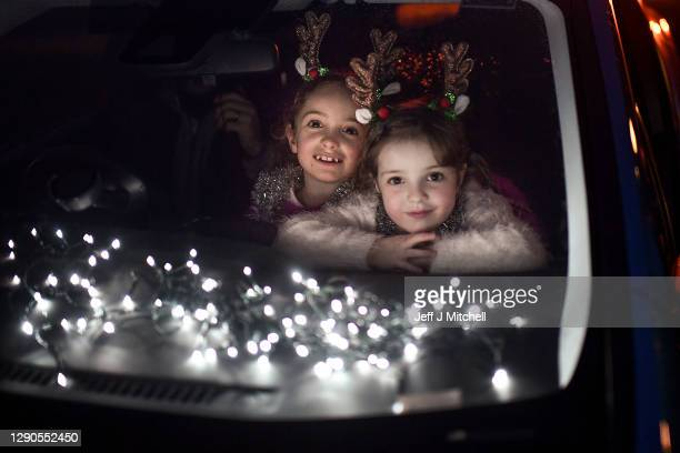 Two young girls look out of the car window as pupils, parents and guardians attend the Kilgarston Girls School drive-in movie on December 10, 2020 in...