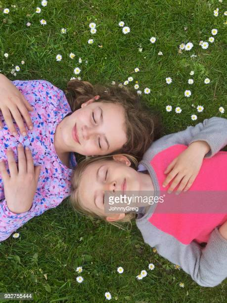 Two young girls lying in grass with daisies, eyes closed