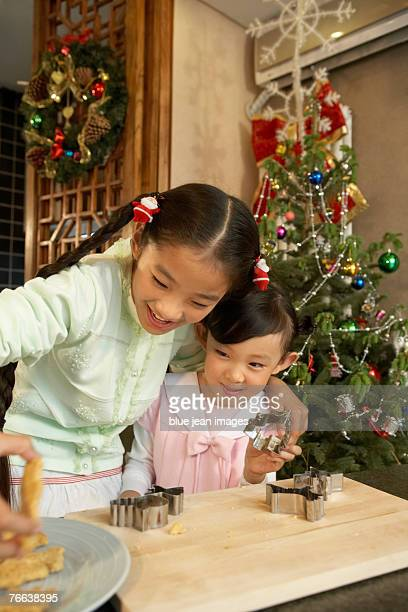 two young girls make christmas cookies. - zakelijke kleding stock pictures, royalty-free photos & images