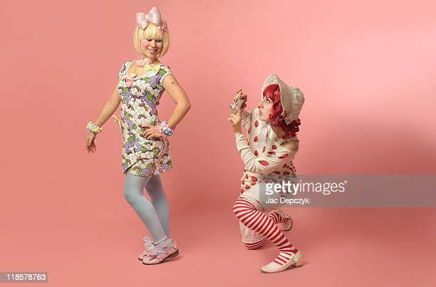 two young girls making fun of photo session - depczyk stock pictures, royalty-free photos & images