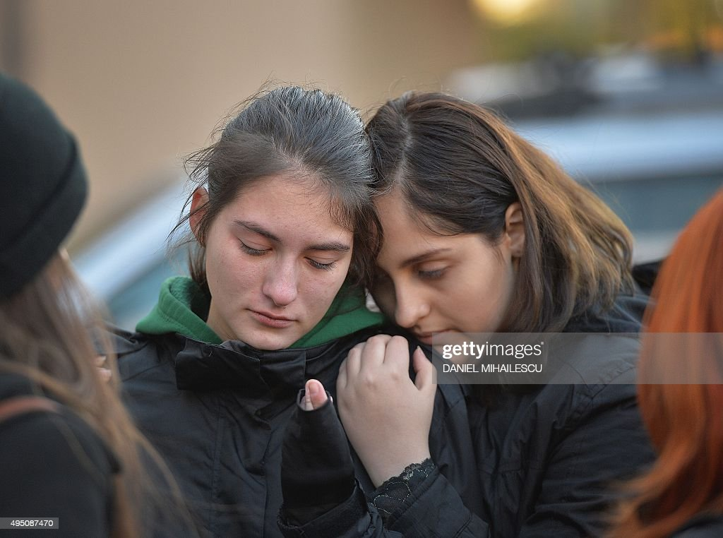 Two young girls mourn a victim at a memorial makeshift outside the nightclub Colectiv in Bucharest on October 31, 2015, a day after a fire broke up. At least 27 people were killed and more than 160 injured after a fire ripped through a nightclub in Bucharest late on Friday, in one of the worst accidents to hit the Romanian capital. MIHAILESCU
