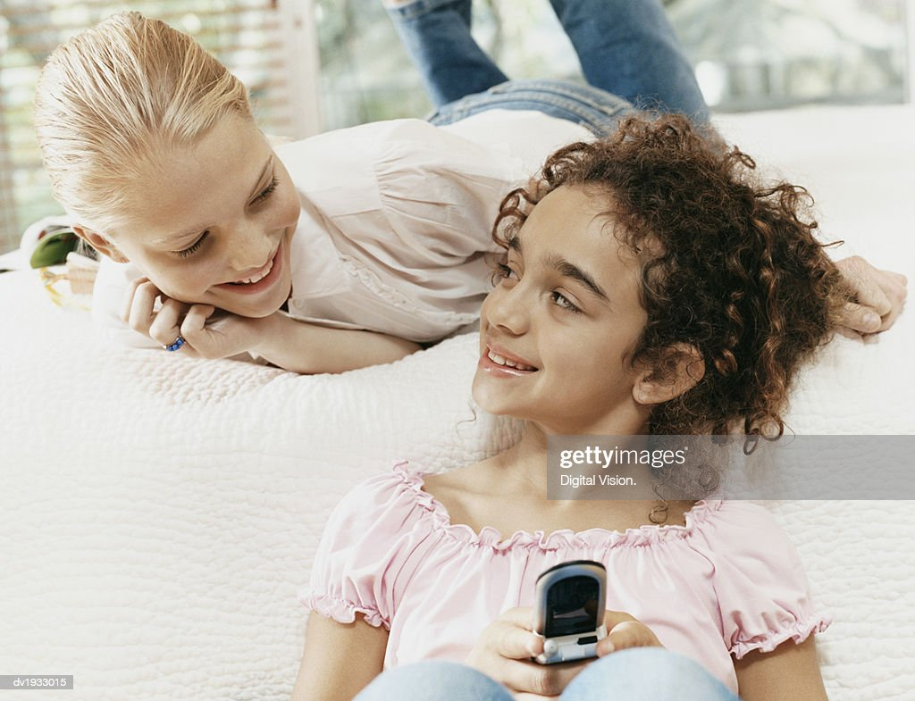 Two Young Girls on a Bed Smiling at Each Other, One Texting on Her Mobile Phone : Stock Photo