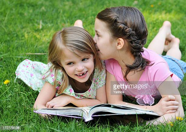 Two young girls on grass reading book whispering