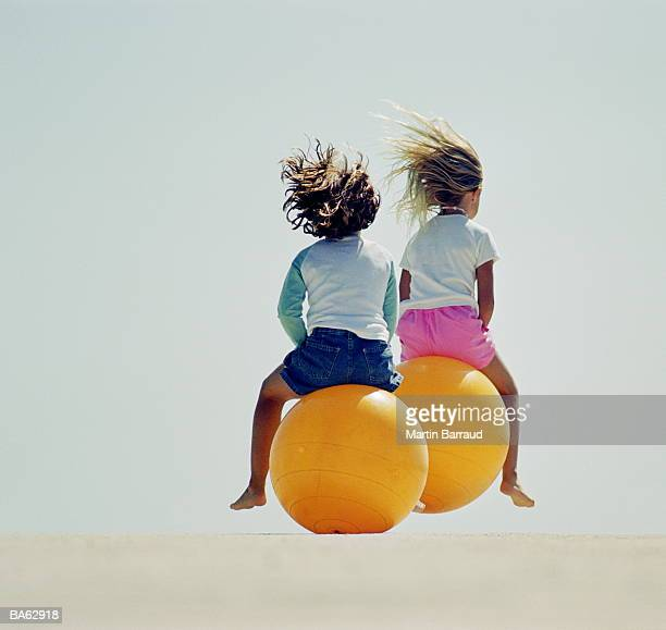 Two young girls (4-7) on space hoppers, rear view