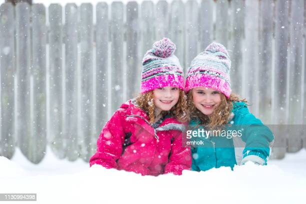 two young girls outside on snowy winter day - pink coat stock pictures, royalty-free photos & images