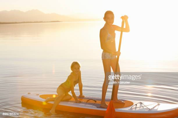 Two young girls paddle boarding on water
