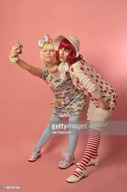 two young girls photograph themselves on pink back - depczyk stock pictures, royalty-free photos & images
