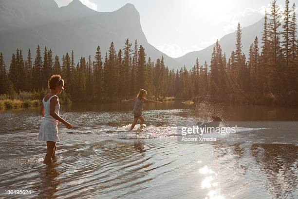 Two young girls play in a mountain pond with a dog