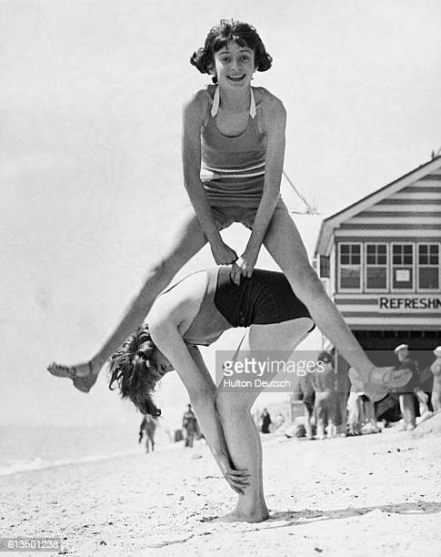 Two young girls play leapfrog on the beach | Location Clacton Essex England UK