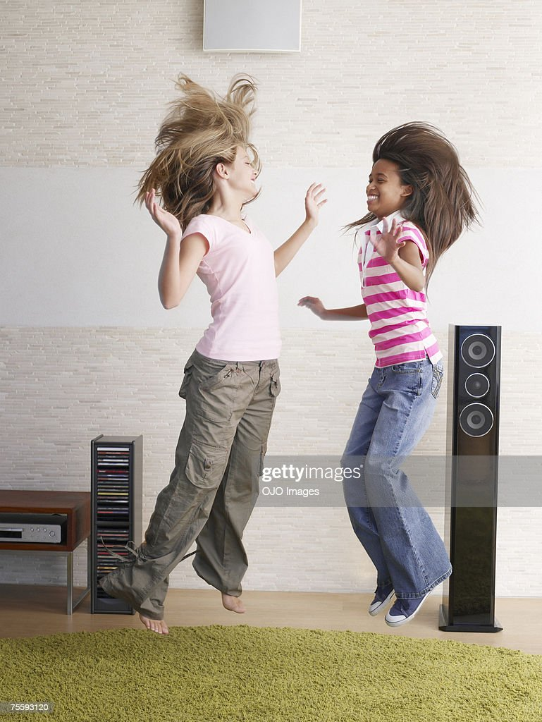 Two young girls playfully jumping around : Stockfoto