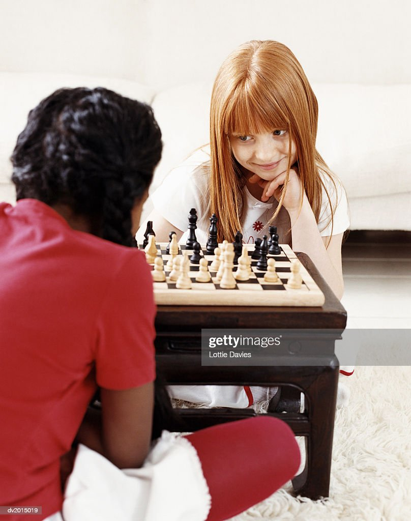 Two Young Girls Playing a Game of Chess : Stock Photo