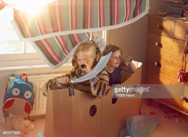 two young girls playing a home made cardboard boat - spelen stockfoto's en -beelden