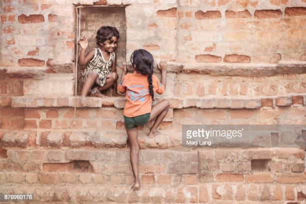 Two young girls playing by a brick wall in Chennai Tamil Nadu India