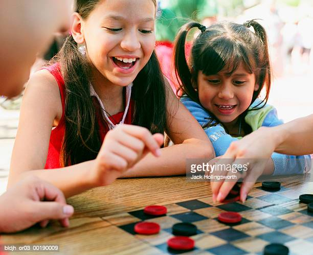 Two young girls playing checkers