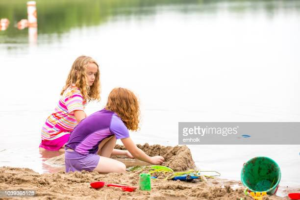two young girls playing in sand & water at beach - lake auburn stock photos and pictures