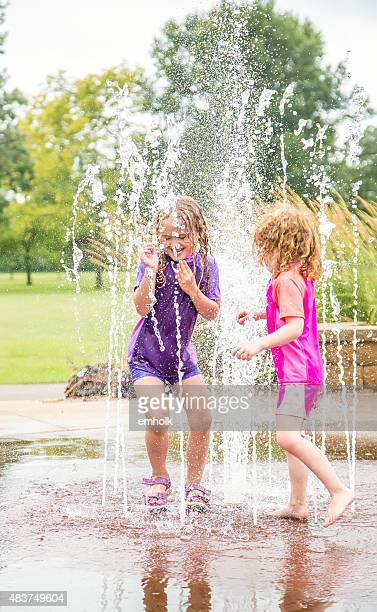 Two Young Girls Playing in Summer Fountains at Splash Park