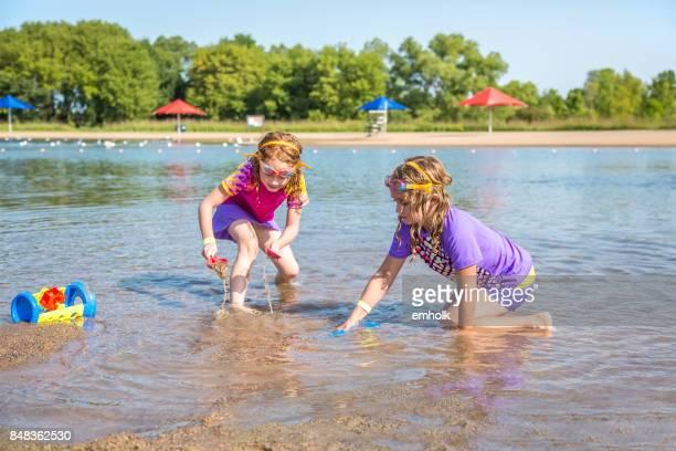 Zwei junge Mädchen spielen im Wasser am Strand