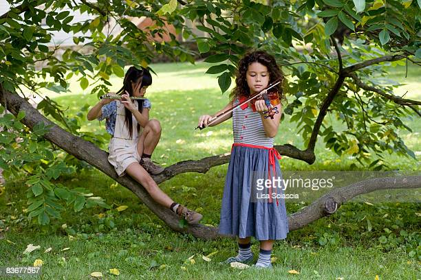 Two young girls playing instruments in nature