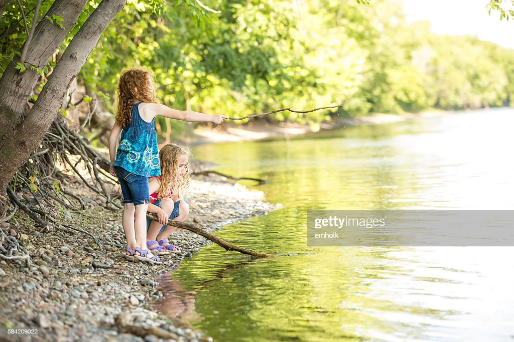 Two Young Girls Playing On Bank of Mississippi River : Stock Photo