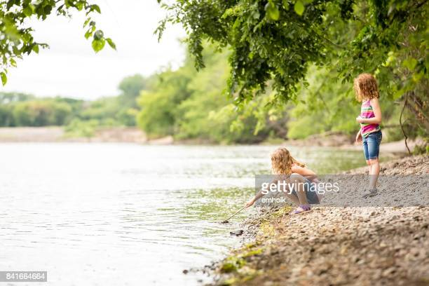 two young girls playing on bank of mississippi river - mississippi river stock pictures, royalty-free photos & images