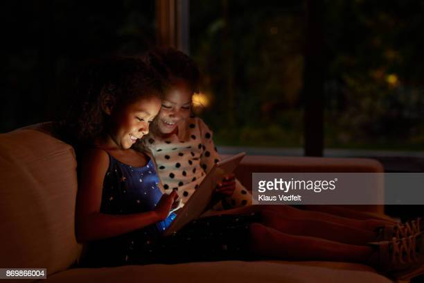 two young girls playing on digital tablet, at night - it movie stock pictures, royalty-free photos & images