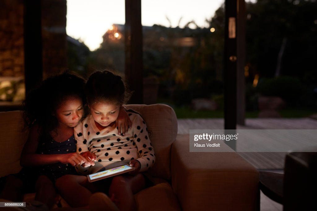 Two young girls playing on digital tablet, at night : Stock Photo