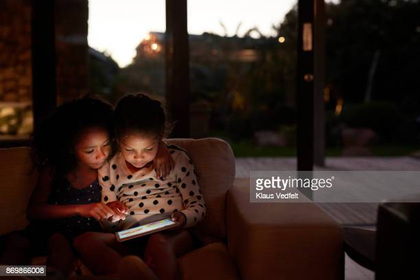 two young girls playing on digital tablet, at night - digital native stock pictures, royalty-free photos & images