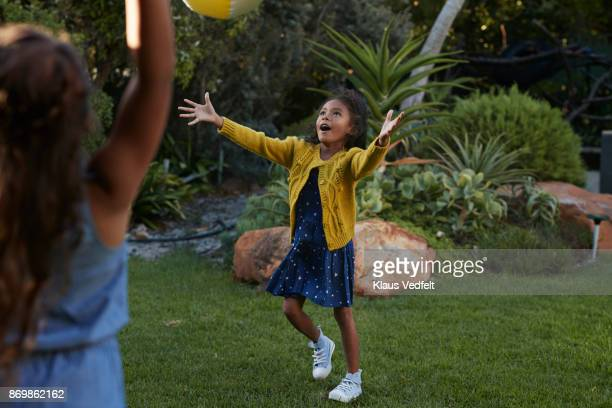 two young girls playing with ball in the garden - catching stock pictures, royalty-free photos & images