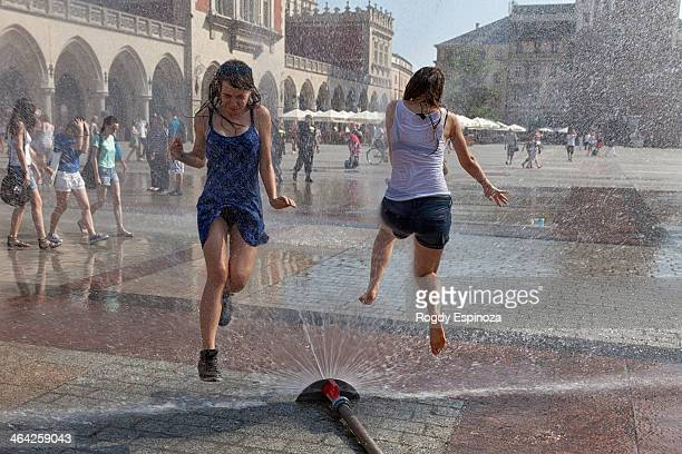 Two young girls playing with water in an old town main square and jumping joyfully above the splashy water.