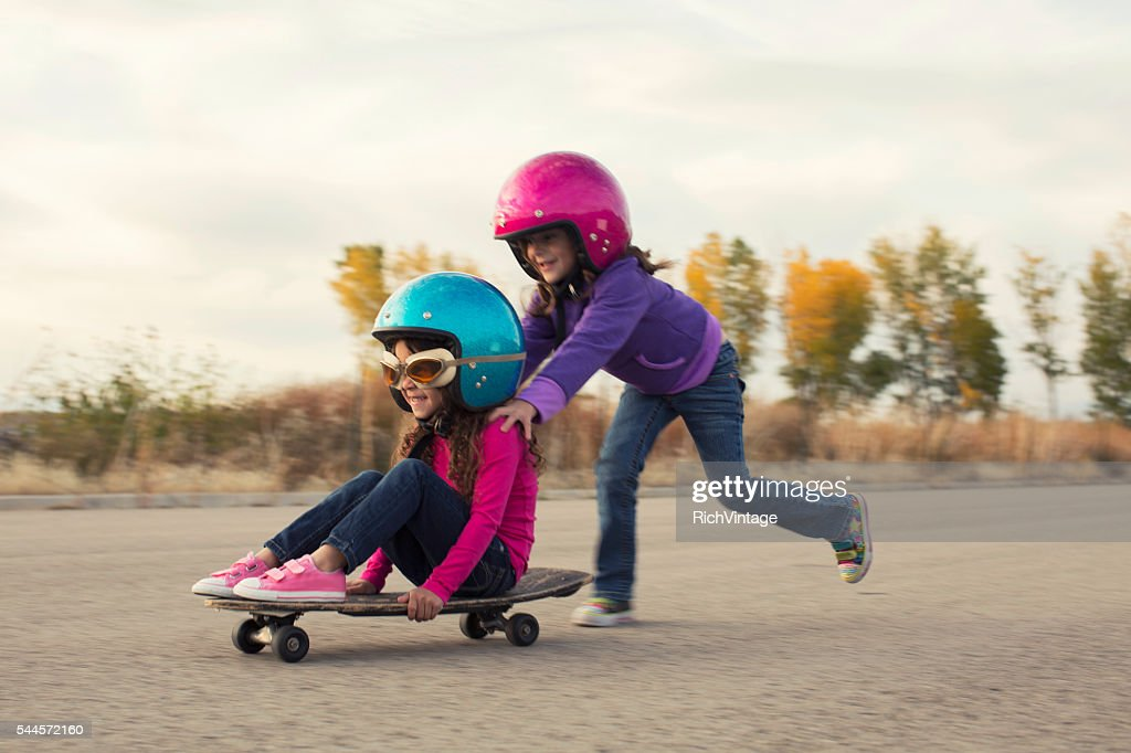 Two Young Girls Race on Skateboard : Stock Photo