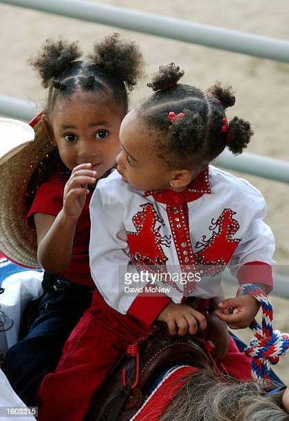 Two young girls ride into the arena at the 18th annual Bill Pickett Invitational Rodeo July 21, 2001 in Los Angeles, CA. The rodeo is named for...