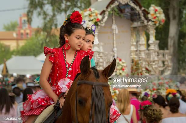 dos jovencitas montando a caballo durante la romería (romería) del rocio en el rocio, españa. - andalucia fotografías e imágenes de stock