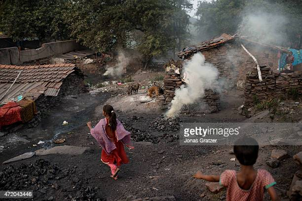 Two young girls running between the huts in their village where methane and other toxic gases spew out from the open wounds in the Earth's crust near...