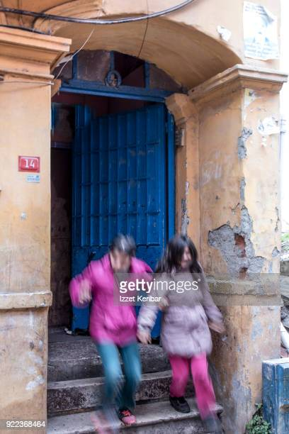 Two young girls rushing out of their home, at Tarlabasi, Istanbul Turkey