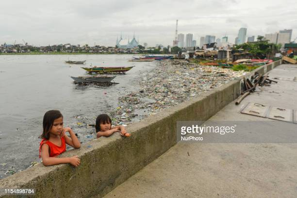 Two young girls seen the Pasig River in Baseco Compound in Manila The Batangas Shipping and Engineering Company Compound is the largest among five...