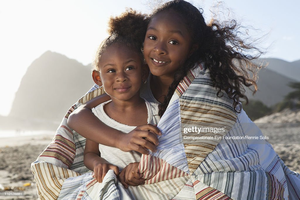 Two young girls sharing a blanket on the beach : Stock Photo