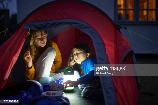 two young girls sharing bowls of food in their tent at night - richard drury stock pictures, royalty-free photos & images
