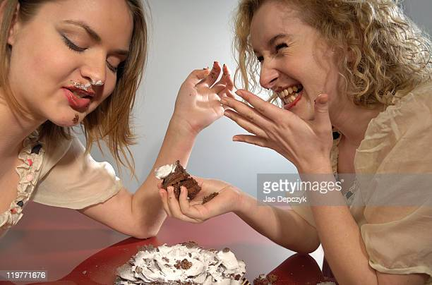 Two young girls sharing chocolate cake.