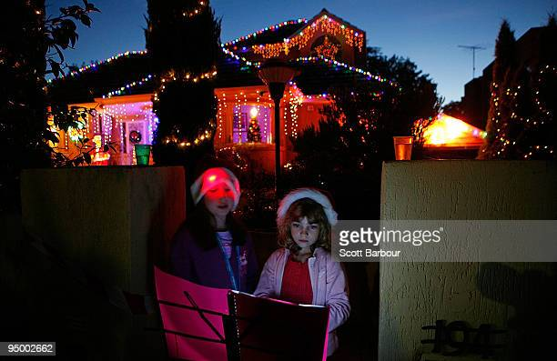 Two young girls sing Christmas carols outside of their house at The Boulevard Christmas Lights Display on December 22 2009 in Ivanhoe on the...