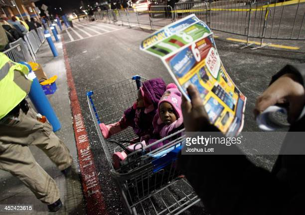 Two young girls sit in a shopping cart as a customer reads looks over the WalMart sales circular before entering the store Thanksgiving day on...