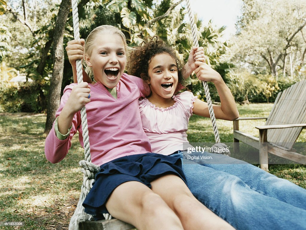 Two Young Girls Sit Side by Side on a Swing in a Garden, Laughing : Stock Photo