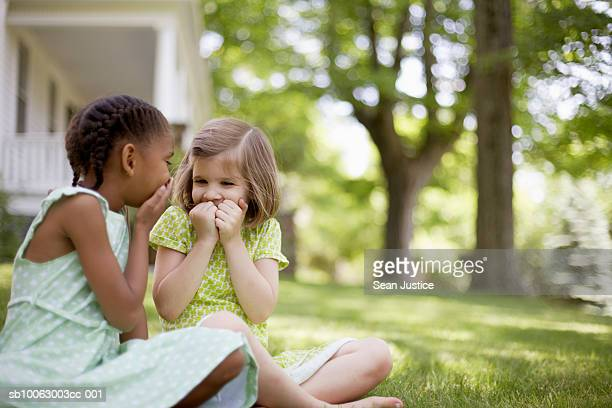 Two young girls (7-8 years) sitting at lawn in front of house, laughing