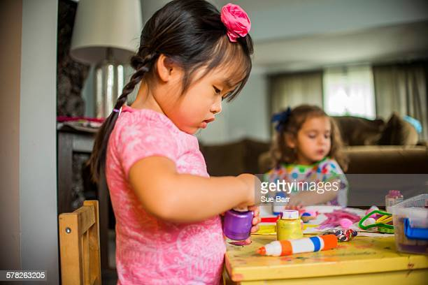 Two young girls sitting at table, making art, using paint