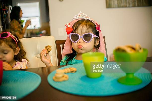 Two young girls sitting at table with drink and cookies