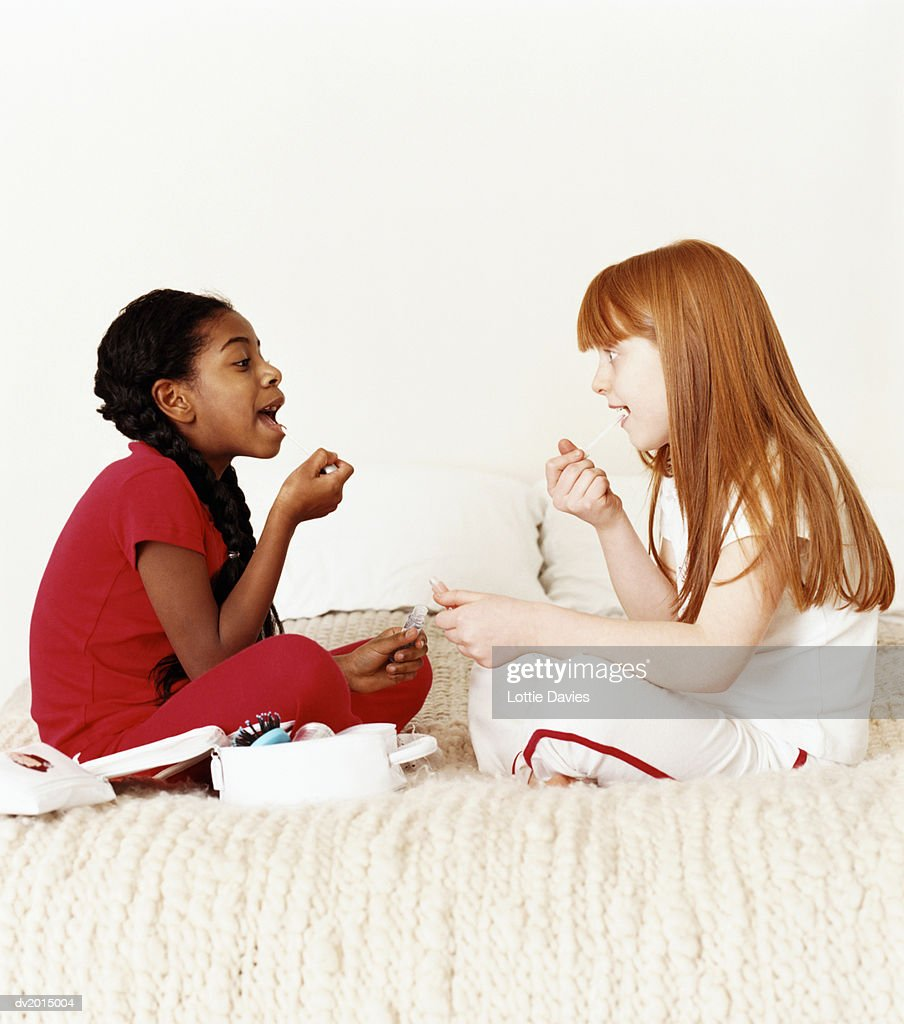 Two Young Girls Sitting Face to Face on a Bed Applying Lip Gloss : Stock Photo