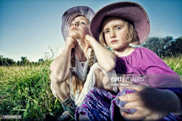 two young girls sitting in a field - robb reece stockfoto's en -beelden