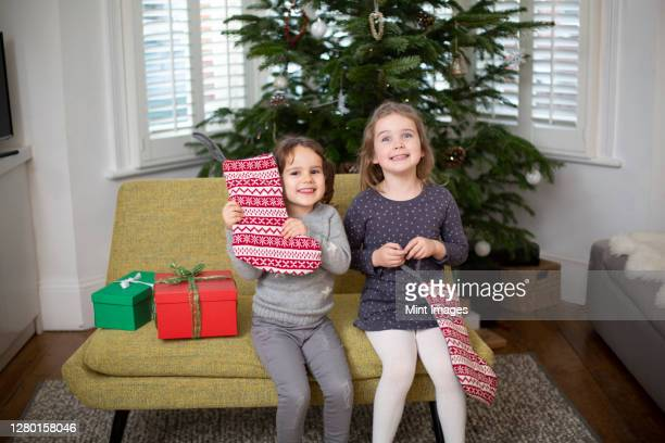 two young girls sitting on sofa in living room, holding red and white christmas stocking - stockings photos stock pictures, royalty-free photos & images