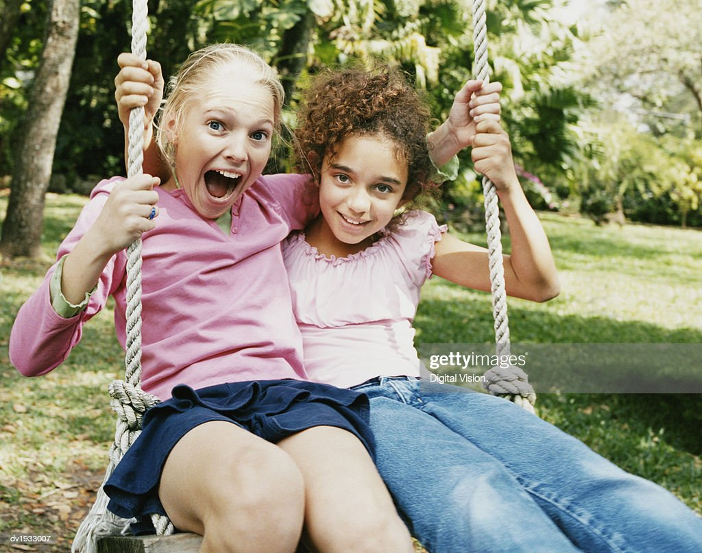 Two Young Girls Sitting Side by Side on a Swing : Stock Photo