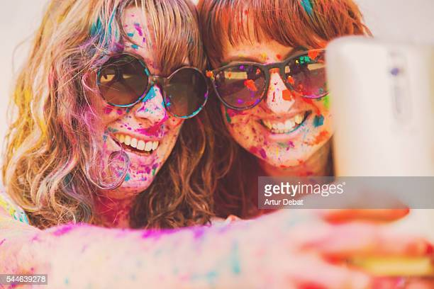 Two young girls smiling and taking a selfie with smartphone covered with colorful Gulal powder during a Holi party to give welcome to the springtime during a sunday family reunion.